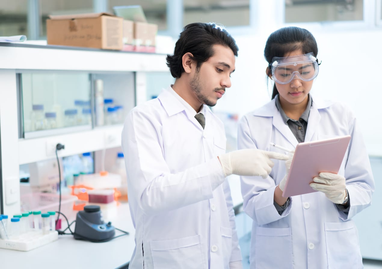 Two lab technicians pointing to a notebook